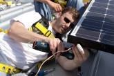 Photo of Brian Borak installing PV panels