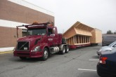 Photo of house framing arriving on a flat bed truck